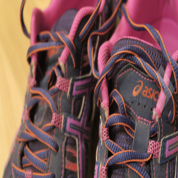 a close up on the laces of the shoes in gray and pink