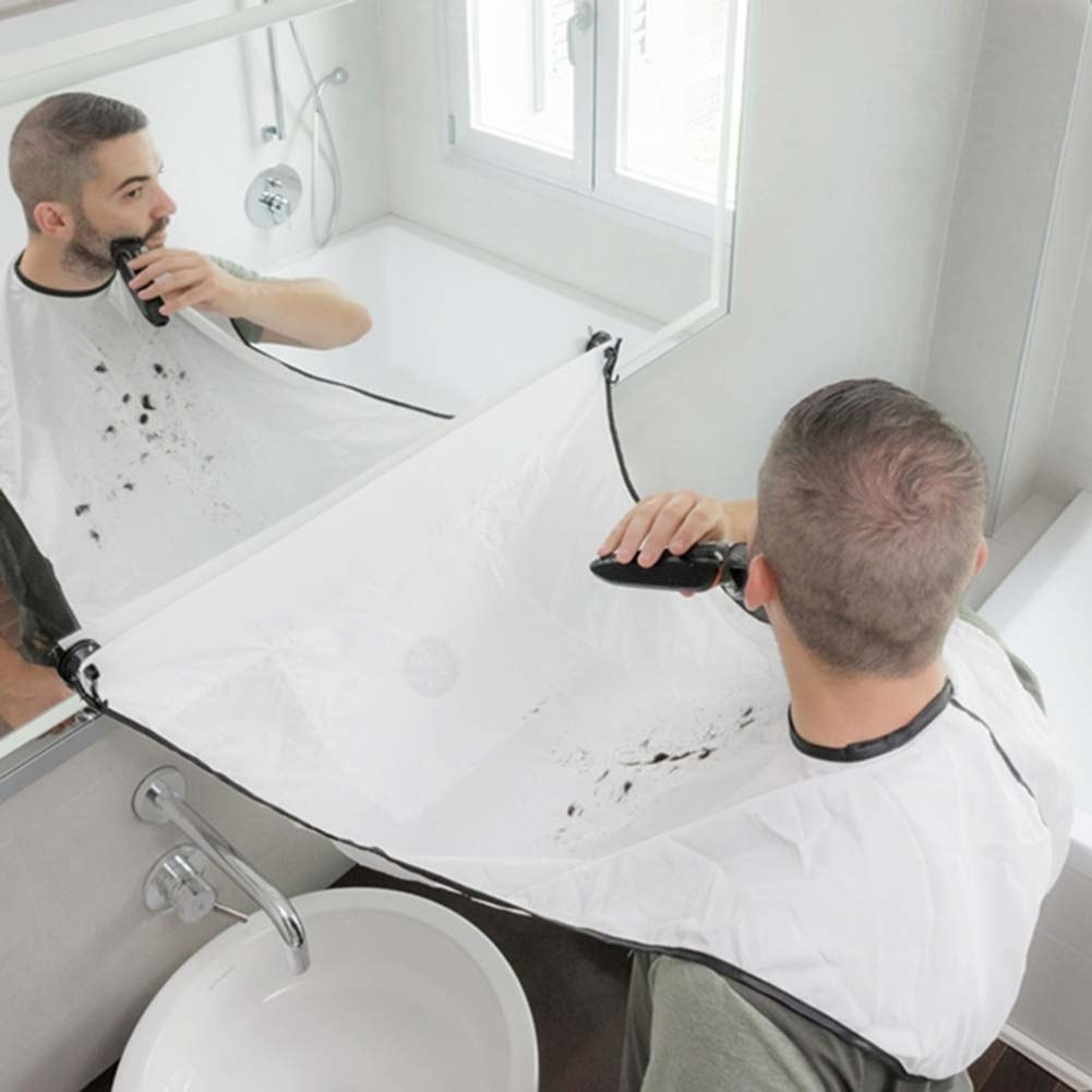 Person shaving with cape around neck and attached to bathroom mirror
