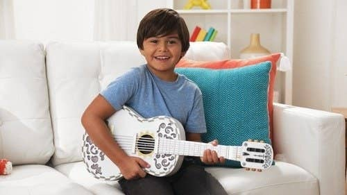 a child holding the guitar