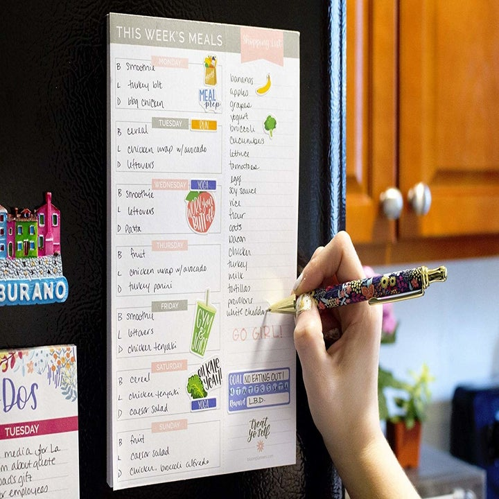 a hand writing on the pad, which is mounted on the fridge with magnets