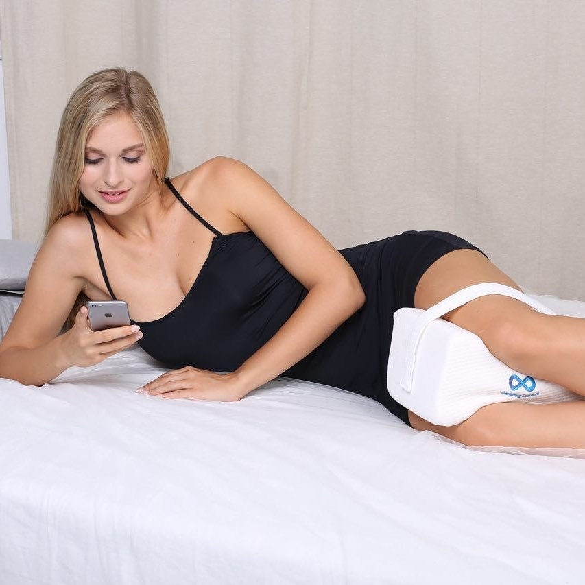 Model wearing the pillow; it's a rectangle with two shallow U-shapes cut out on both of the longer sides and the strap goes above the knee