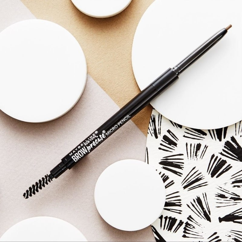 The brow pencil showing the narrow tip and spoolie brush on the other side