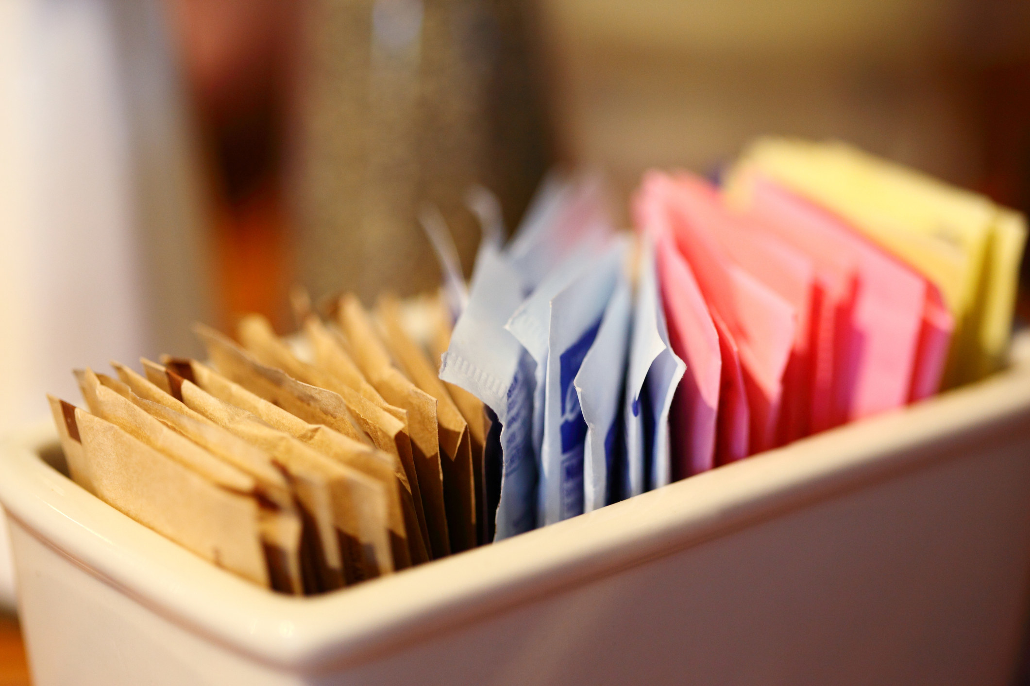 A close up of a dish holding various different sugar packets