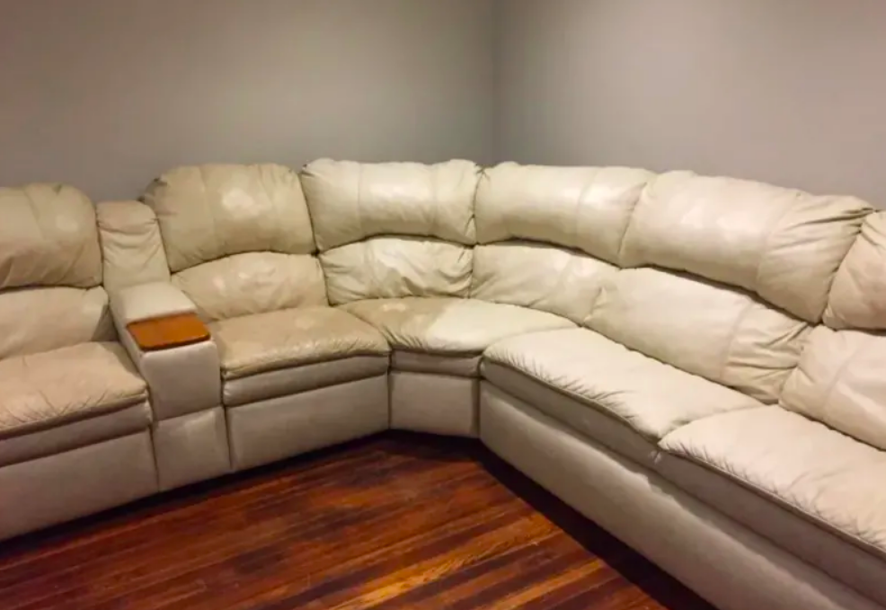 Leather sectional worn to a darker tan in uncleaned areas and warm white in spots that have already been cleaned