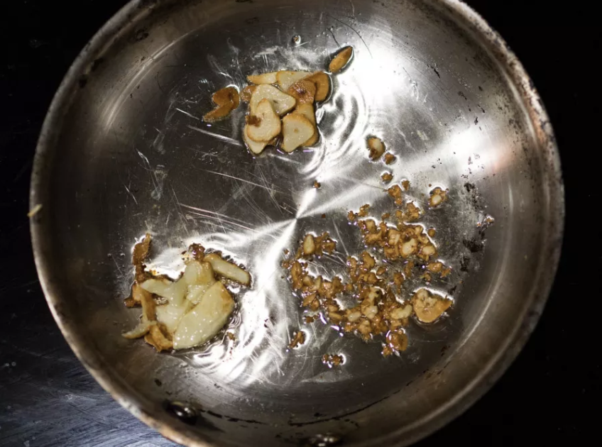 A stovetop pan with burnt garlic in it