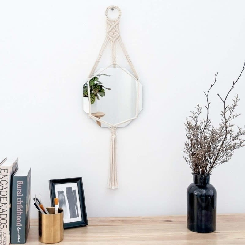 Small hexagon shaped ivory macrame mirror hanging from a wall