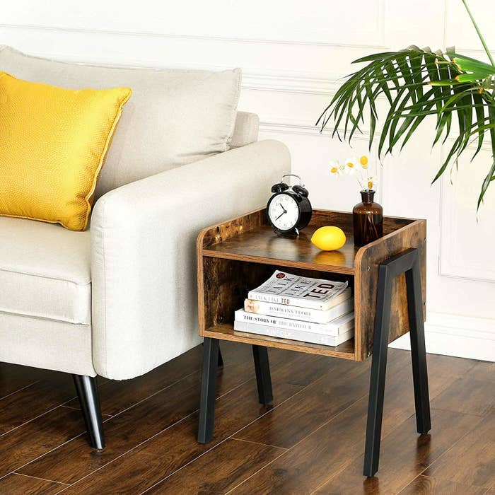 Wood end table with an open shelf and black metal legs next to a couch.