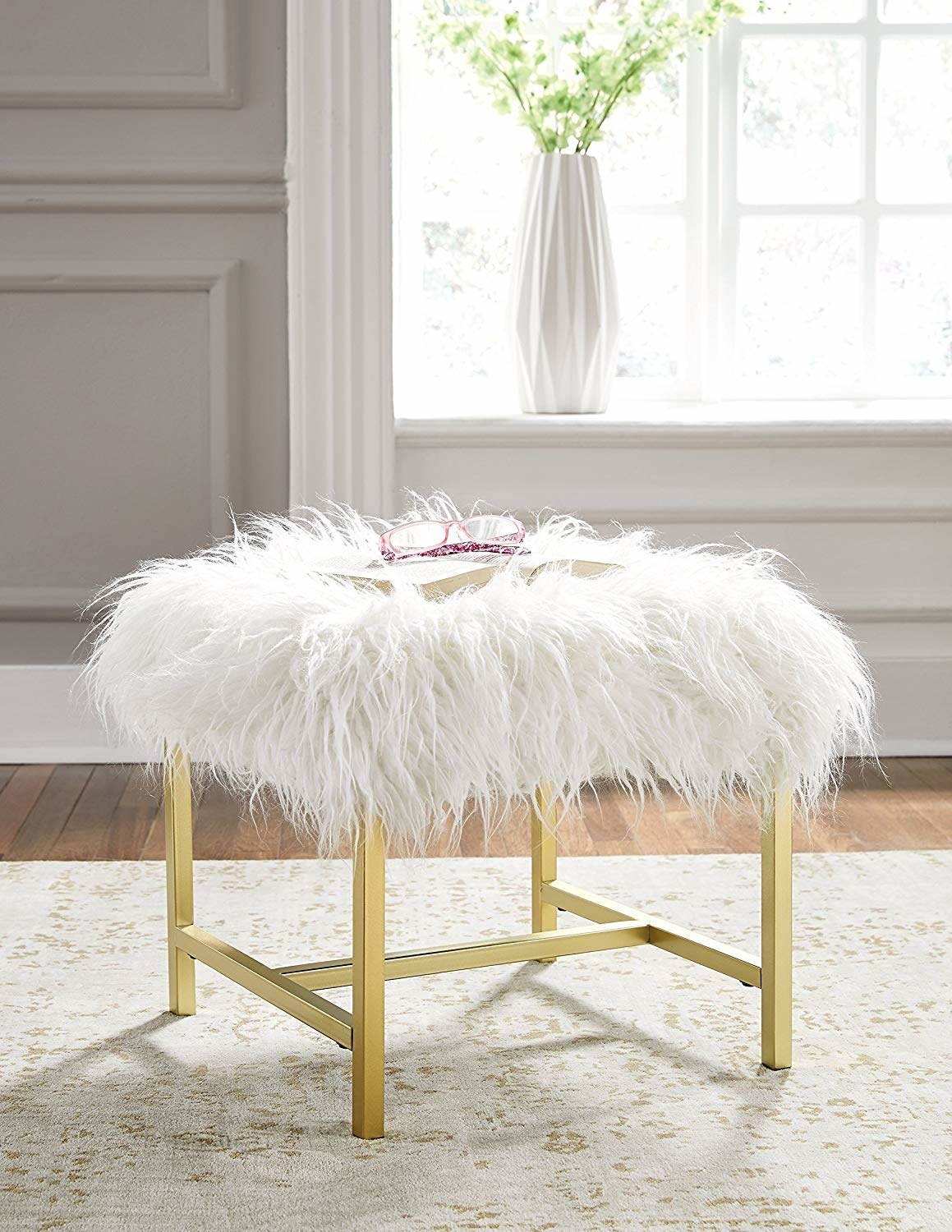 A square-shaped stool with white faux fur on top and gold acrylic legs