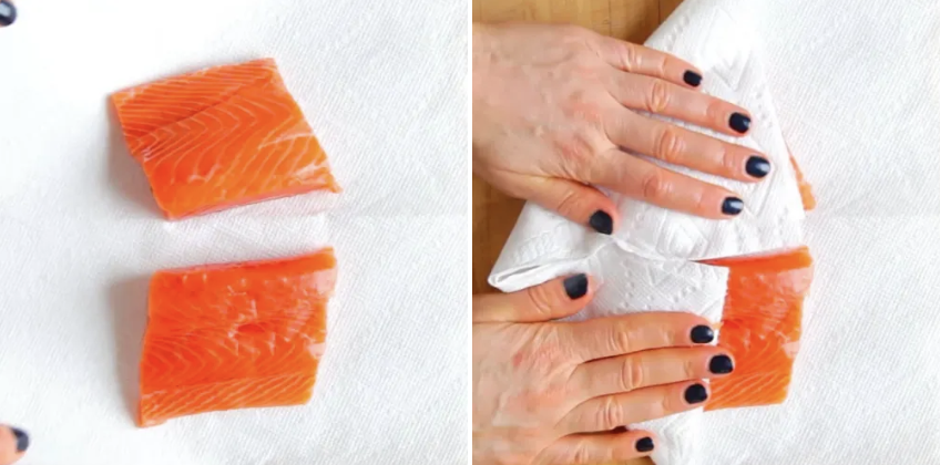 Two salmon fillets being dabbed with a paper towel