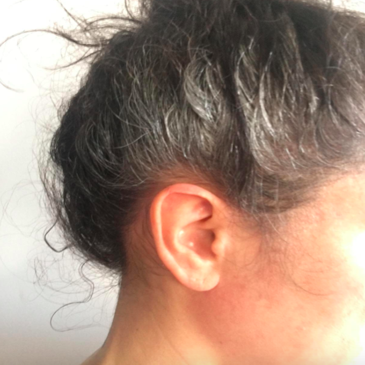 person wearing their hair in a high bun with flecks of silver in otherwise dark hair