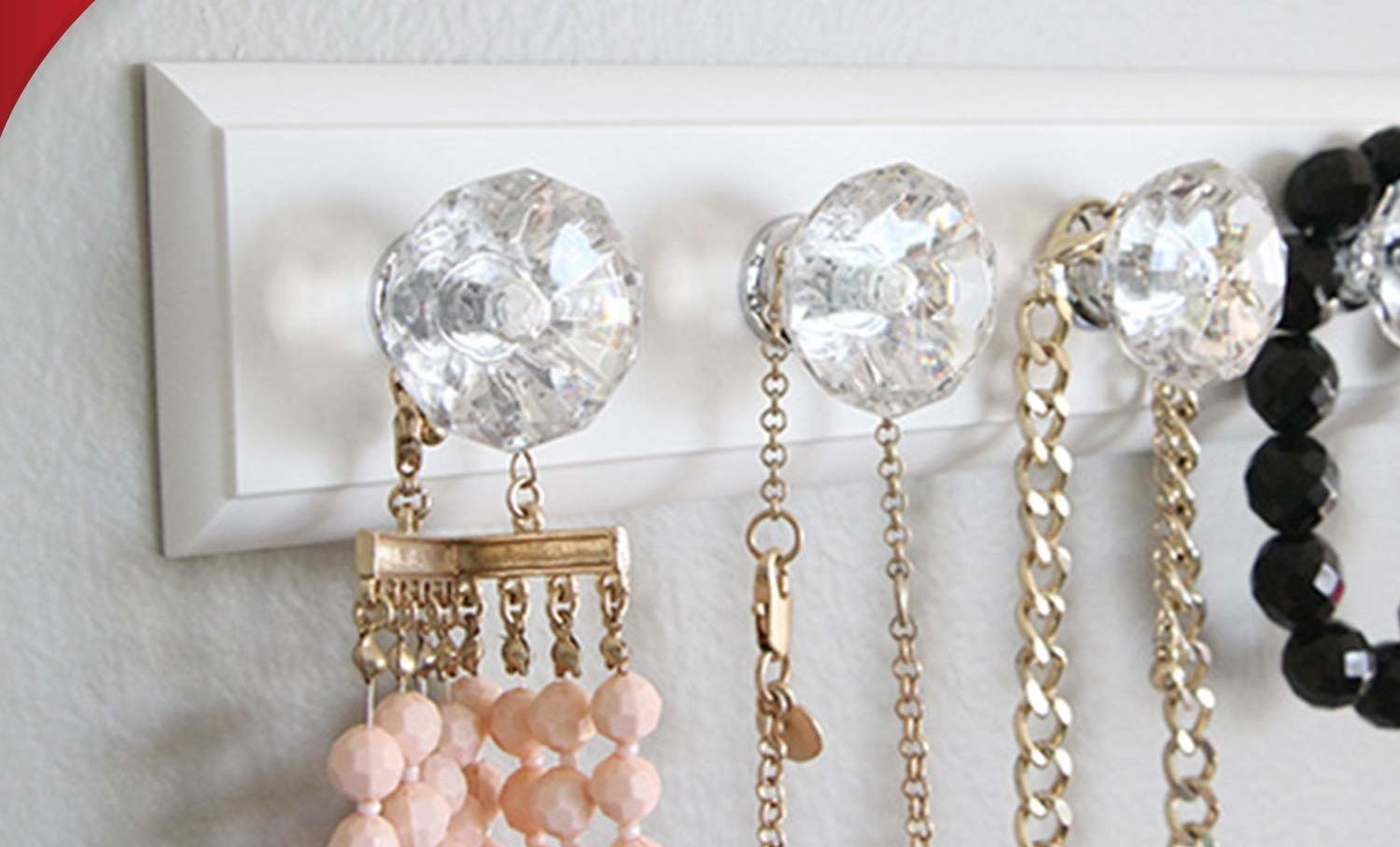Four necklaces hanging from a rack with four knobs