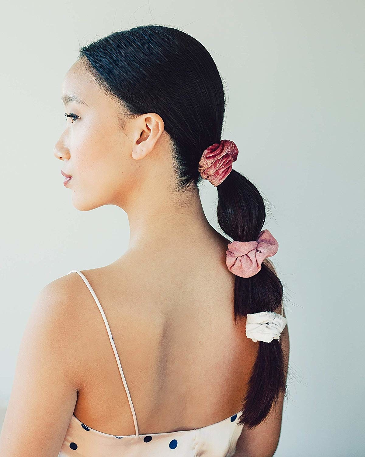 Model with a long ponytail with three scrunchies along the length in dark pink, light pink, and white