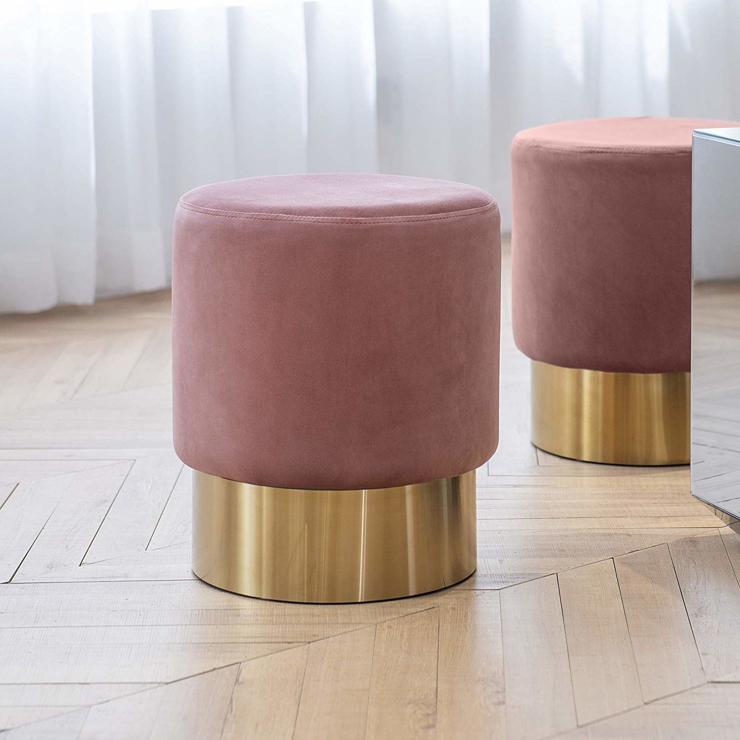 Two circular blush-colored ottomans with gold foot bands