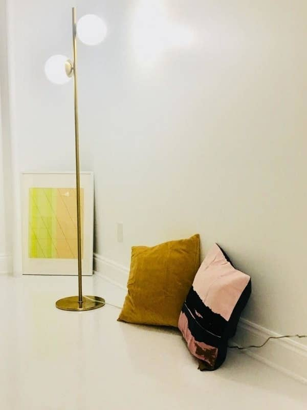 Reviewer pic of the tall gold lamp with two circular bulbs coming out the side