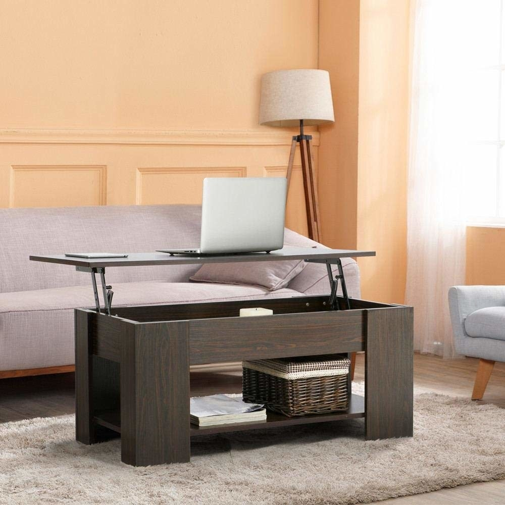 The brown coffee table with a shelf at the bottom and thick inner area with the top lifted up, with a laptop on top, showing how you can use it as a workstation