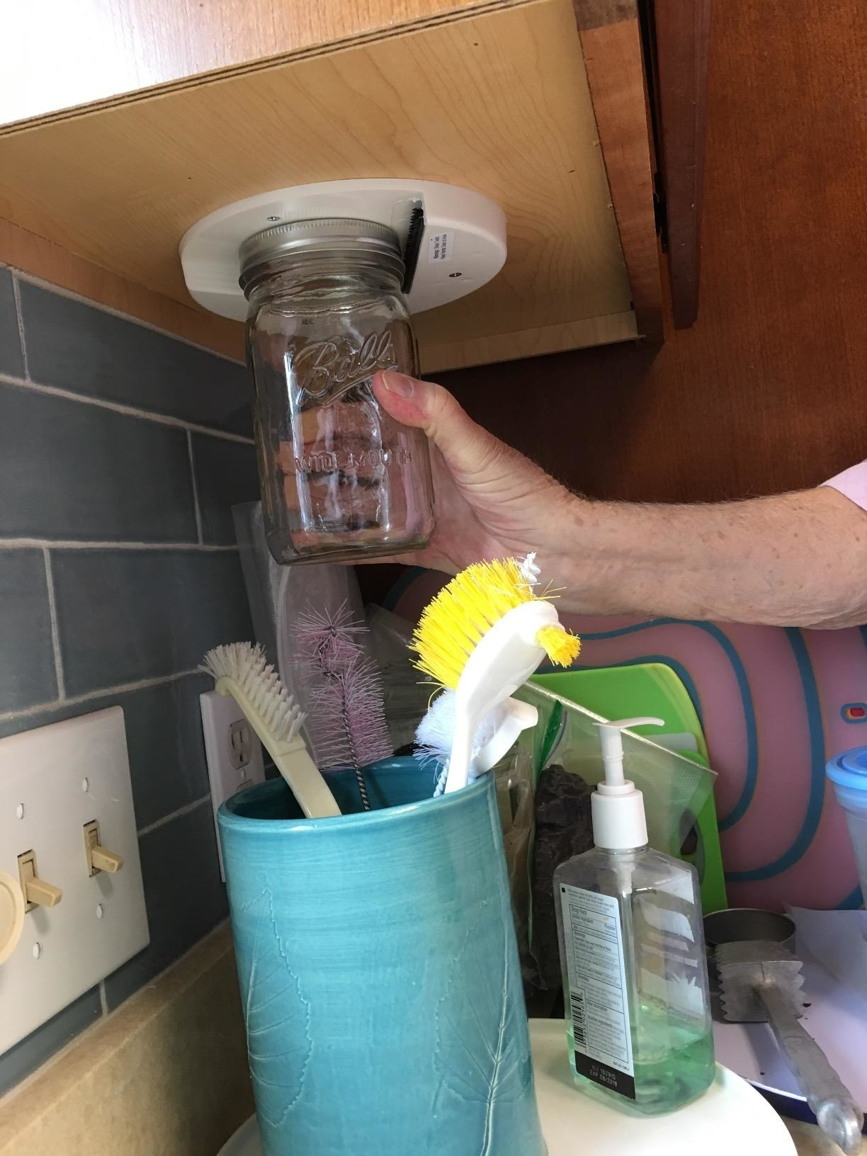 Reviewer using the jar opener, which they've attached to the bottom of a cabinet, to open a mason jar