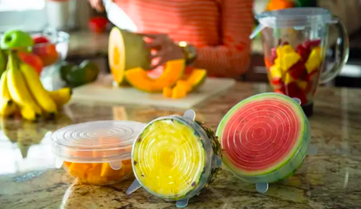 Bowl of melon, half a pineapple, and half a watermelon covered by silicone lids