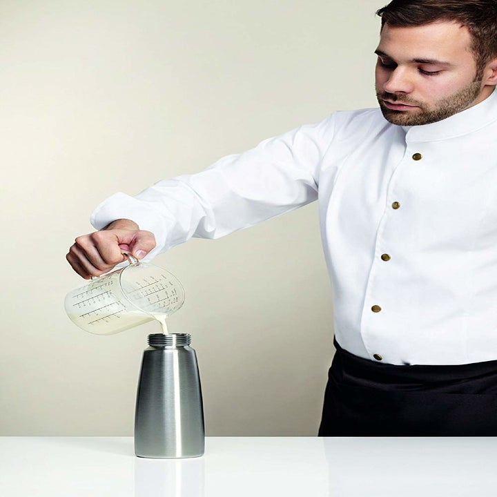 Person pouring cream into stainless steel container