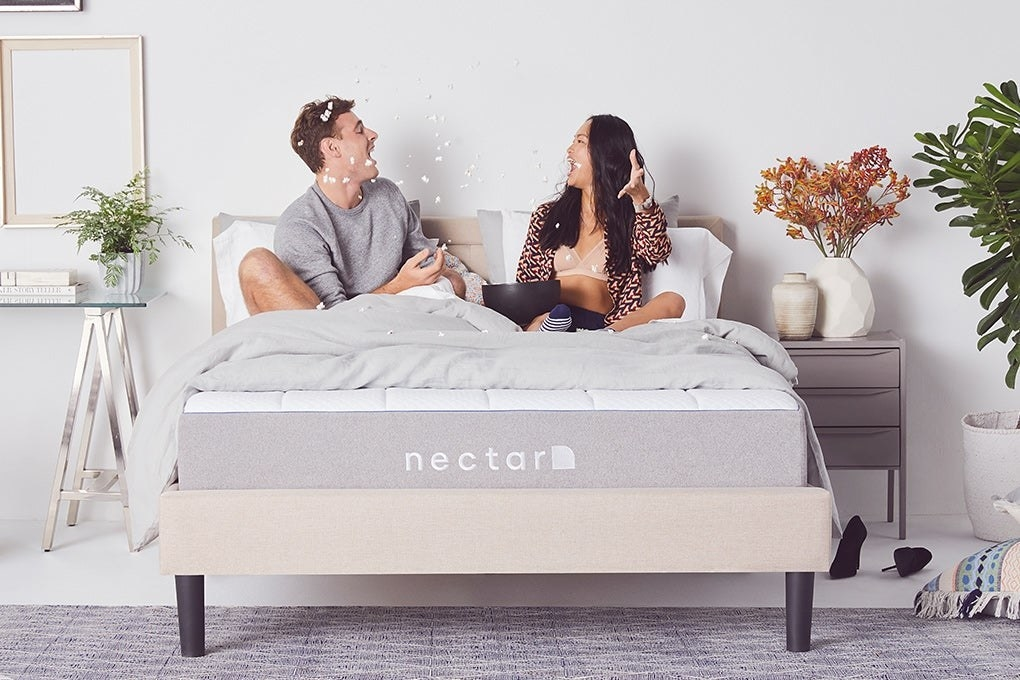 Two people sitting on top of the mattress