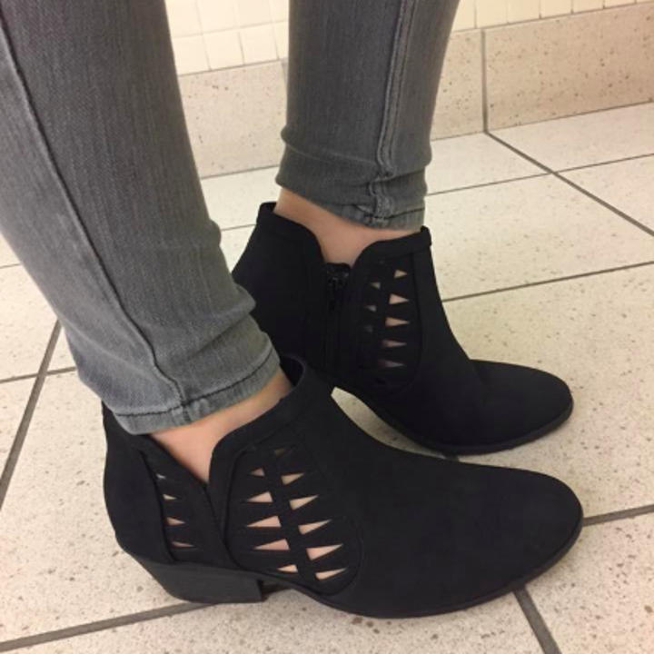 A reviewer wearing the very low heel black booties with triangular cutouts