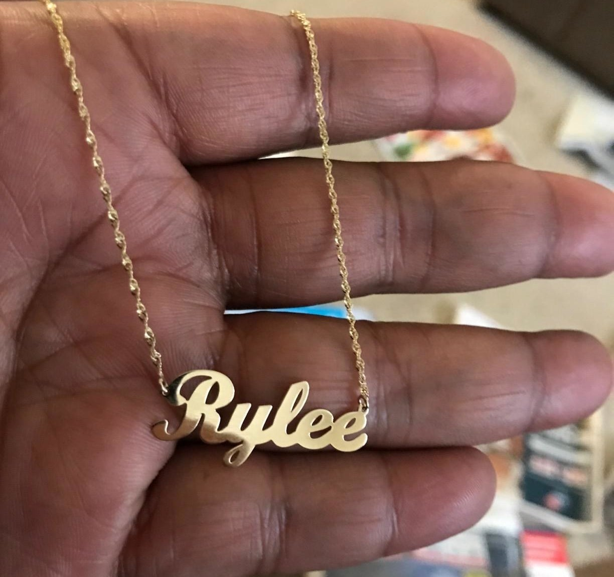Reviewer holding the necklace, which shows their name in cursive