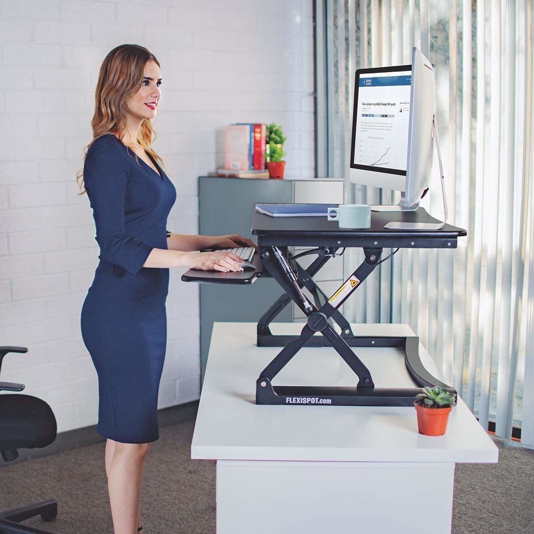 Model using the standing desk on top of an actually desk, which is supporting two desktop computers