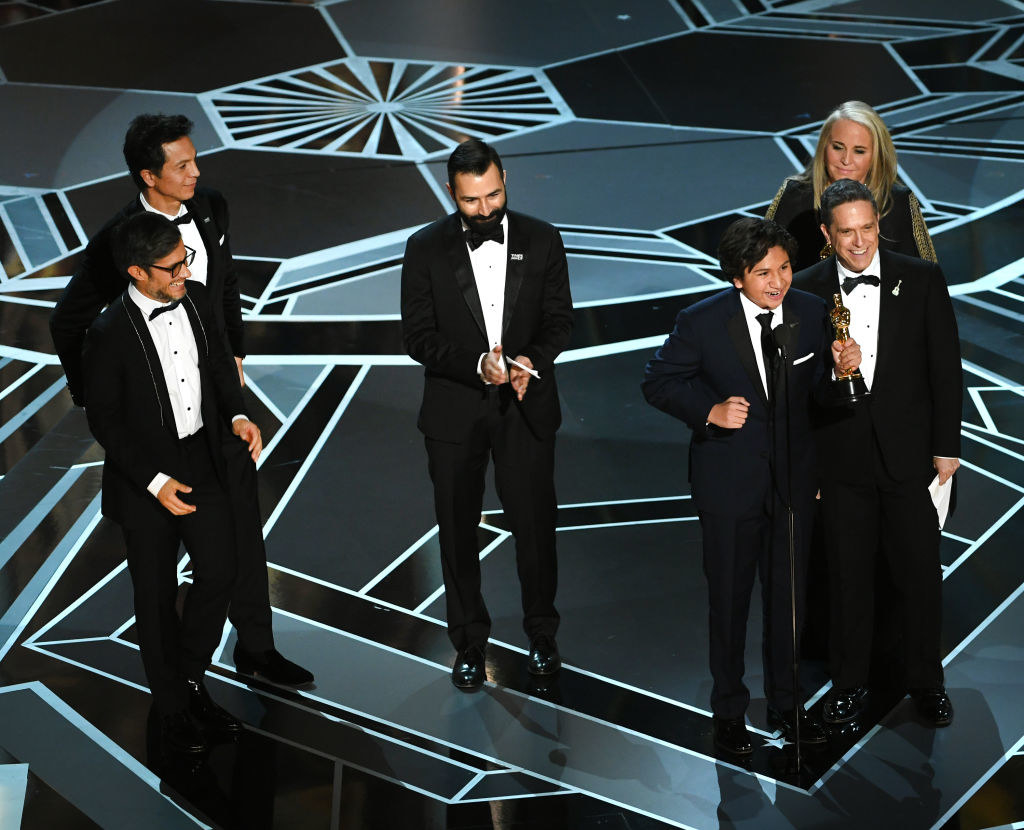 The producing team and cast members accepting the Oscar for Best Animated Feature