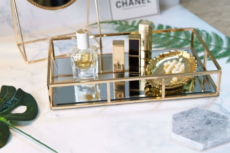 tray styled on vanity holding makeup and perfume