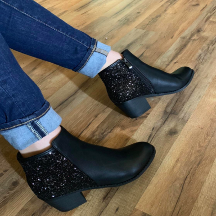 A reviewer wearing the low-heeled booties in black with cuffed jeans