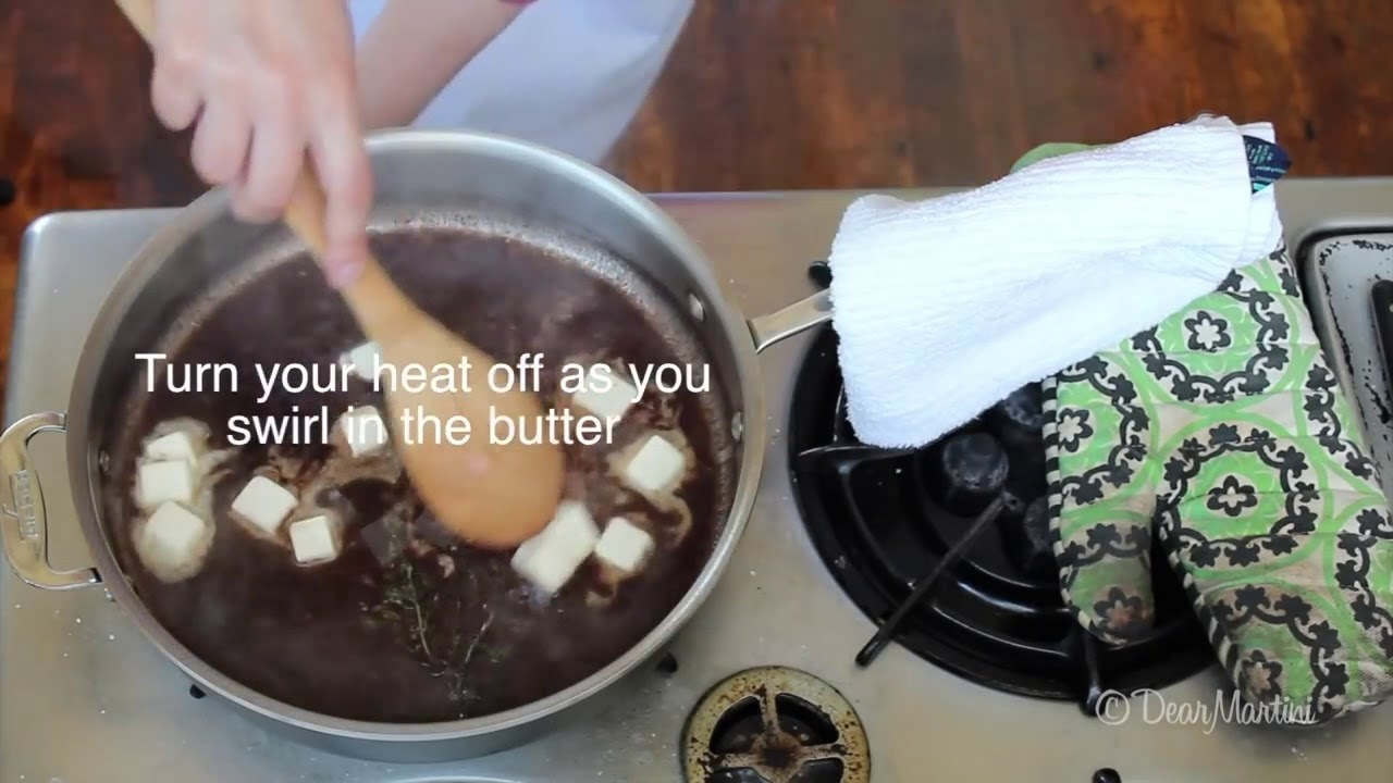 A cook swirling pats of butter into a stovetop steak sauce