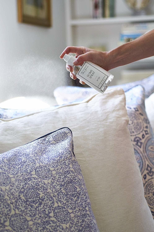 Hand spraying Home Spray onto pillow