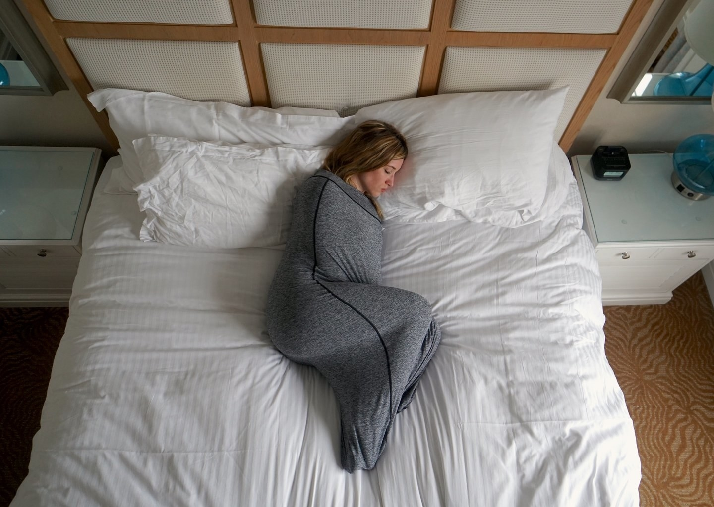 Model curled up in bed with a sleep pod