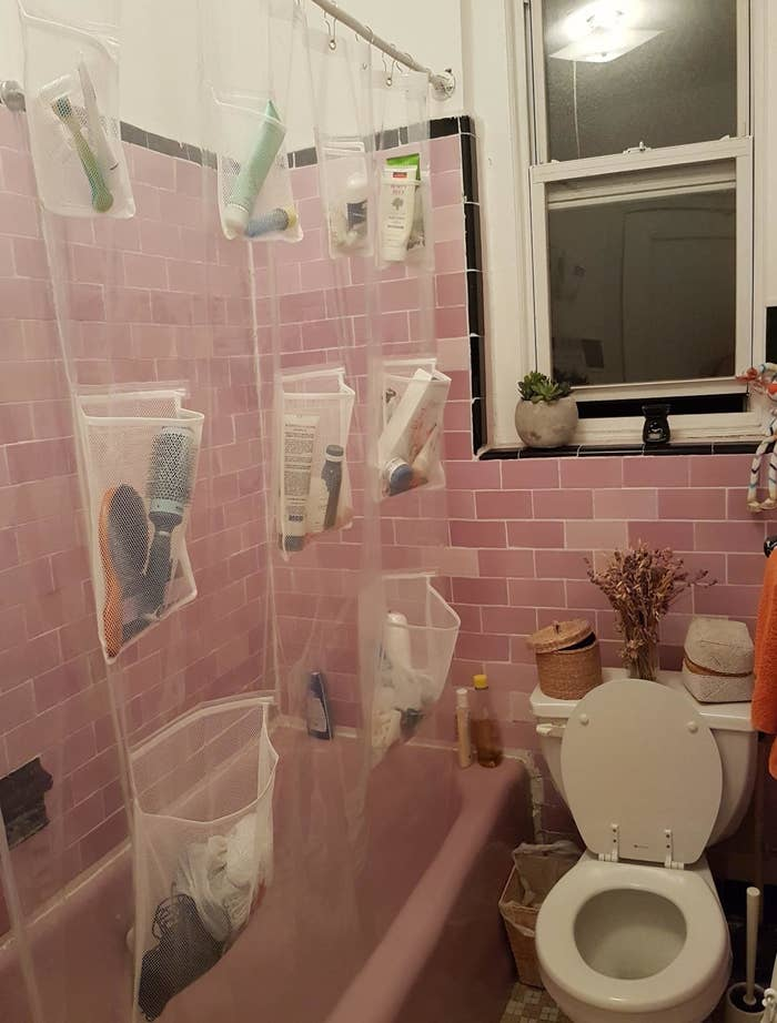 Reviewer image of the shower curtain with a variety of shampoos, hair brushes, and other bathroom items stored in the pockets