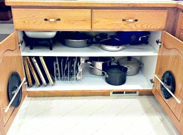lower open kitchen cabinet with small curtain rods on the inside of the door to hold pot lids