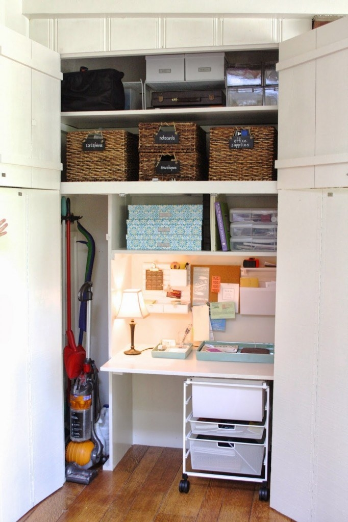inside of a home office closet with storage bins on shelves above, and a broom organizer on the wall out of the way