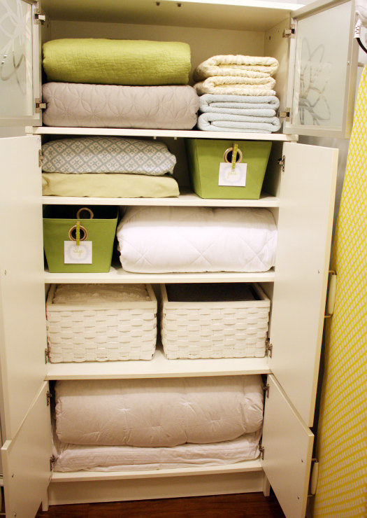 inside a linen closet with stacks of bedding, storage boxes, and labeled bins