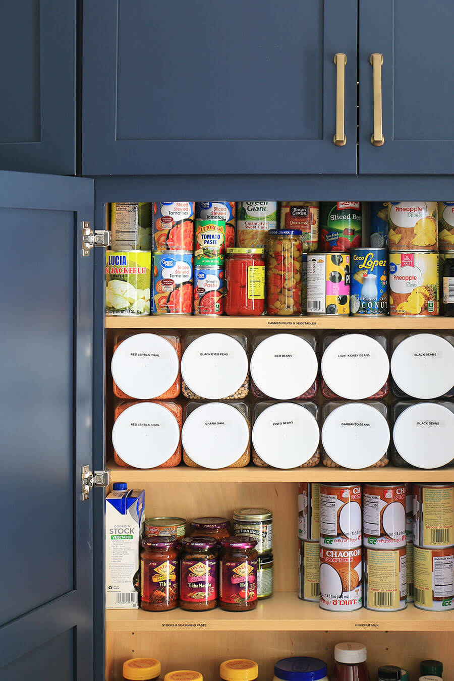 open kitchen pantry cabinet with cans and jars, plus plastic food containers that are squared off so you can stack them horizontally
