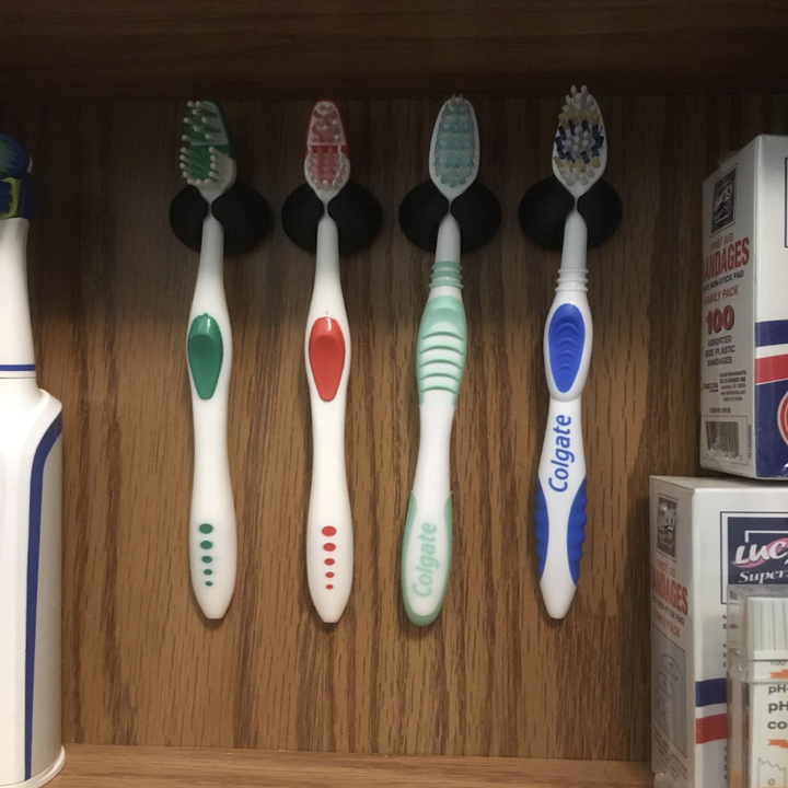 clips being used to hold toothbrush in cabinet
