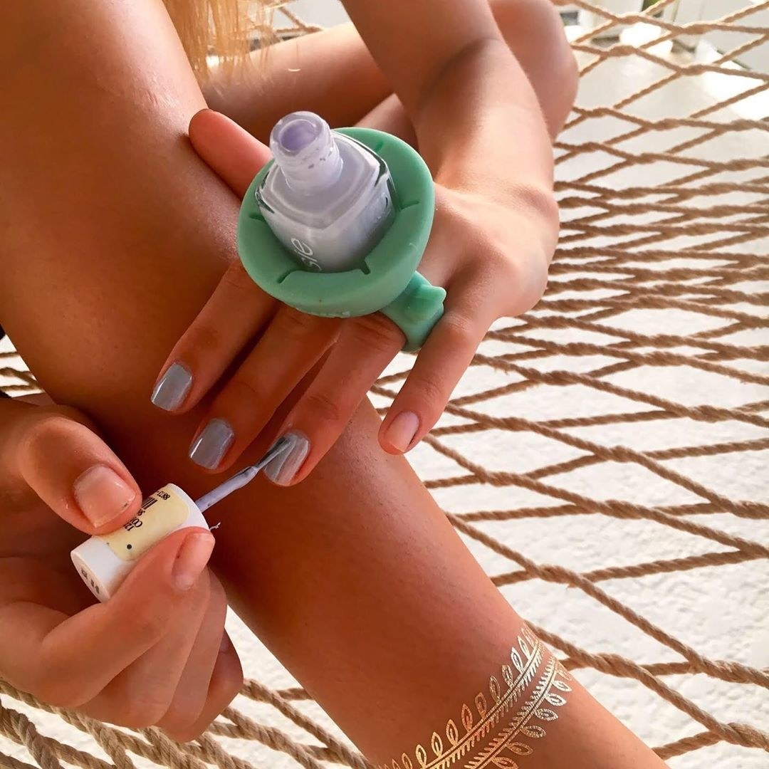 model wearing blue ring with purple nail polish bottle inside