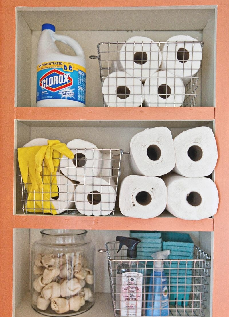 inside a cabinet with wire baskets filled with cleaning items, toilet paper, and other various household goods