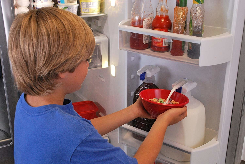 Child pushing bowl of milk against tap, dispensing milk from jug without picking it up
