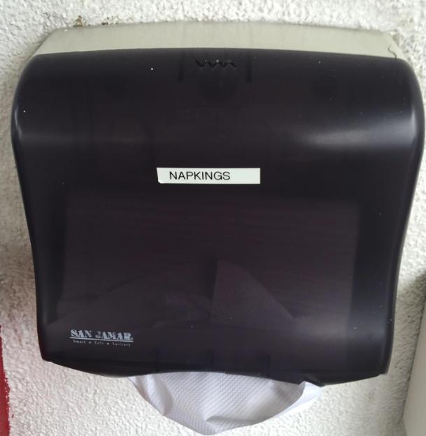 "Paper towel dispenser labeled ""napkings"""