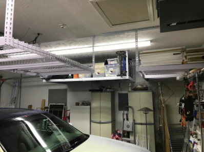 reviewer pic of the shelves attached to the ceiling of a garage with plenty of room to park underneath the shelves