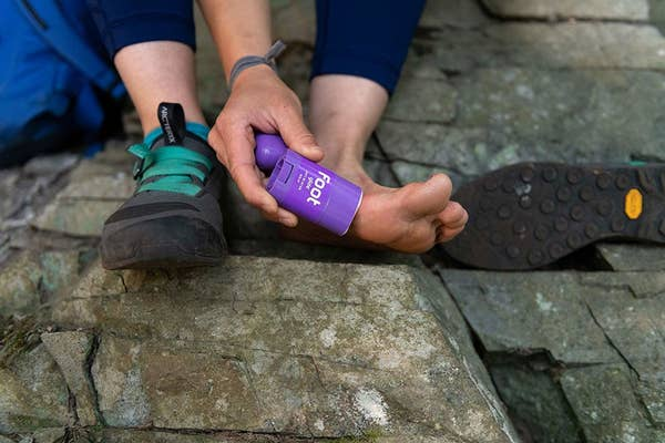 Person applying product to foot while hiking