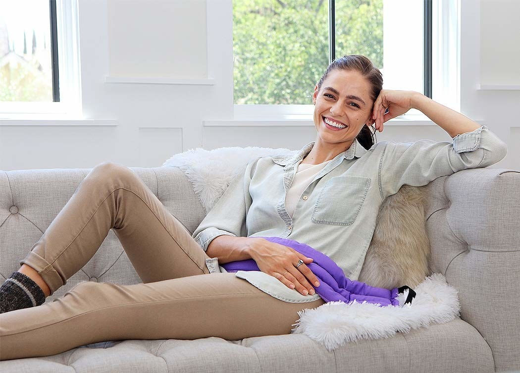 A person lies on a couch with the heating pad over their abdomen
