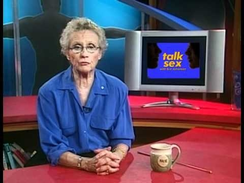 Sue Johanson in a blue shirt, sitting at a red desk on the set of her TV show Talk Sex