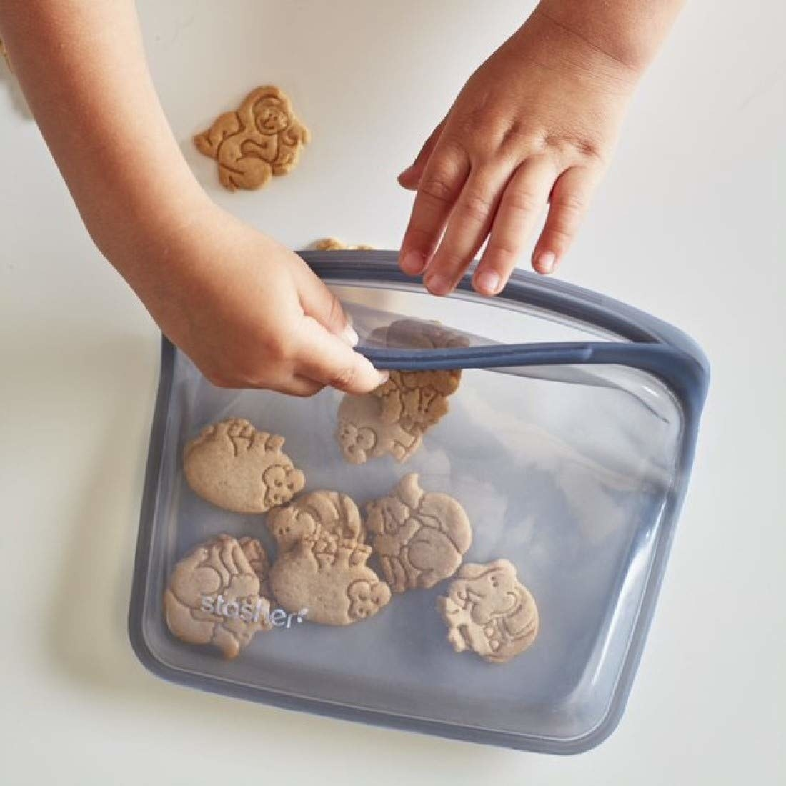 child's hand reaching for animal crackers in the gray bag