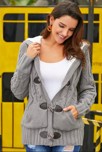 model wearing a gray chunky cardigan with toggles up the front that's also lined in faux fur