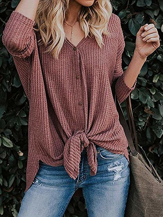 model wearing dusty rose color waffle knit button up shirt that ties in the front styled with some distressed jeans