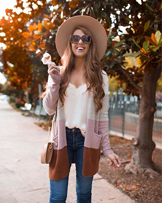 model wearing  jeans, a cami, and the multicolor gray, brown, and pink cardigan in fall hues